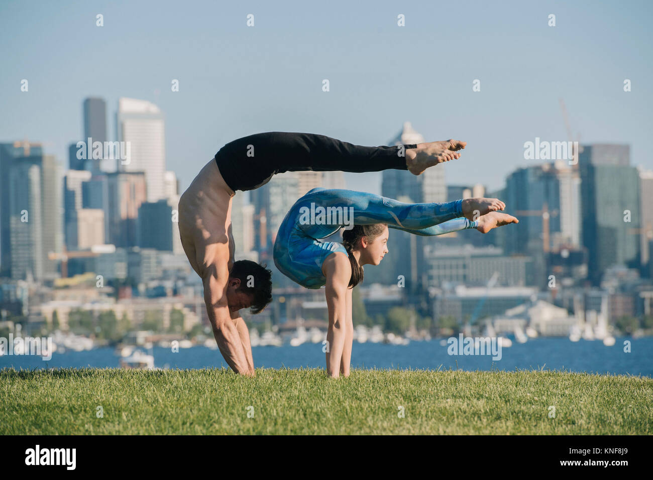 Teenage girl and young man, outdoors, balancing on hands in yoga position - Stock Image
