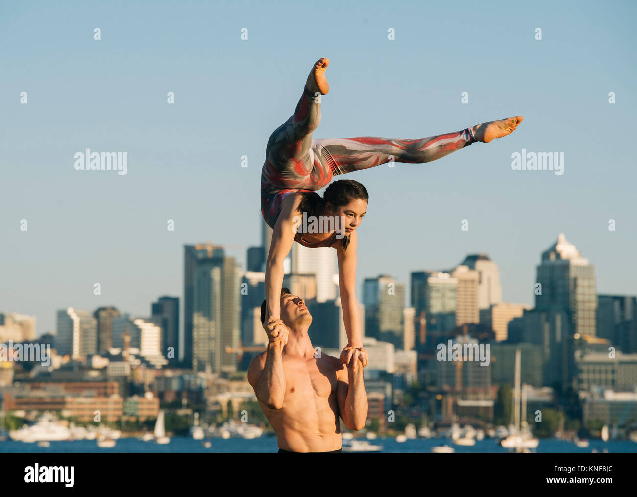 Teenage girl and young man, outdoors, woman balancing on man's hands in yoga position - Stock Image
