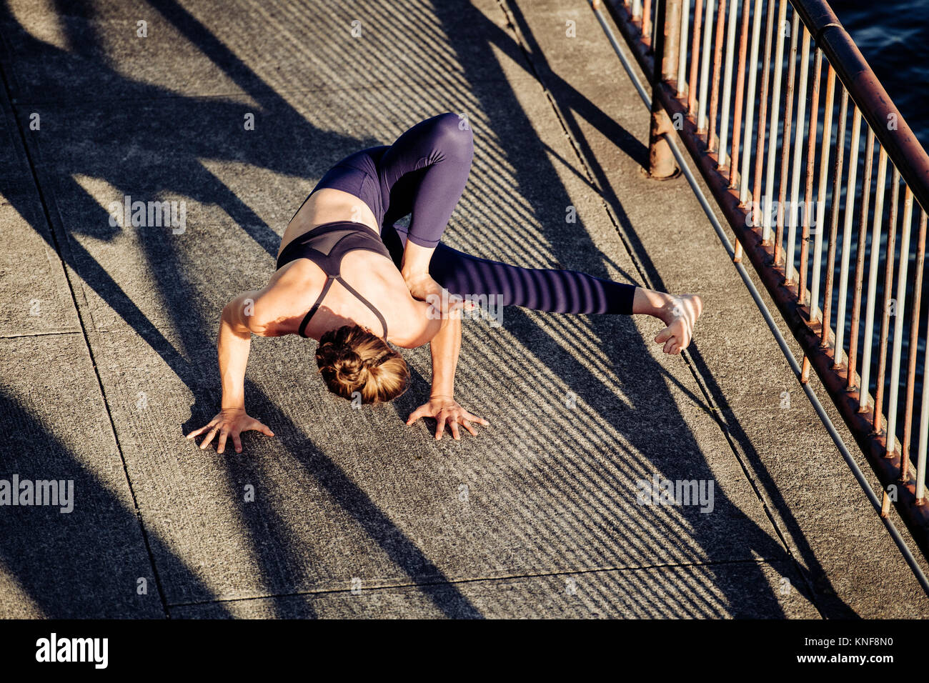 Young woman outdoors, in urban setting, in yoga position, elevated view - Stock Image
