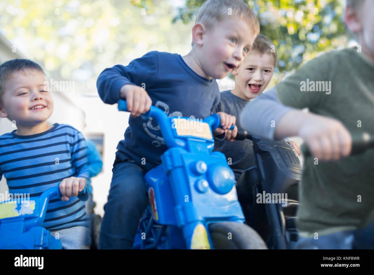Boys at preschool racing push motorbikes in garden - Stock Image