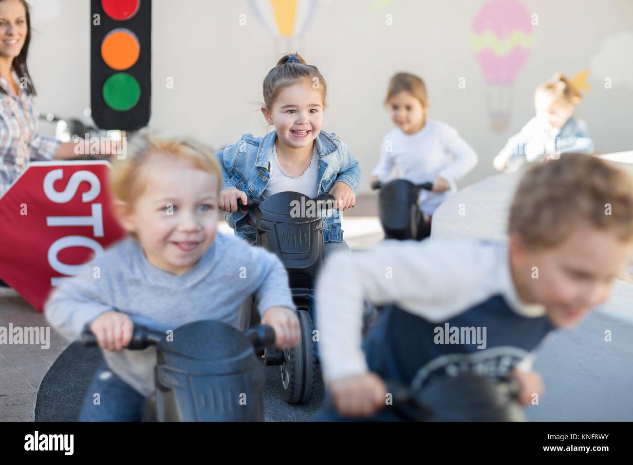 Boys and girls at preschool, racing push motorbikes in garden - Stock Image