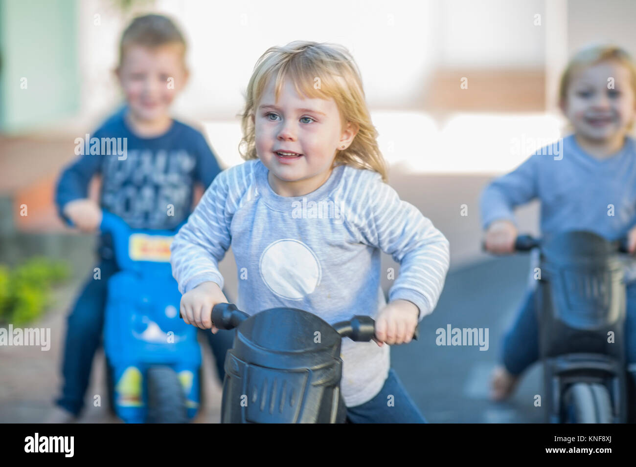 Girl and boys at preschool, racing push motorbikes in garden - Stock Image