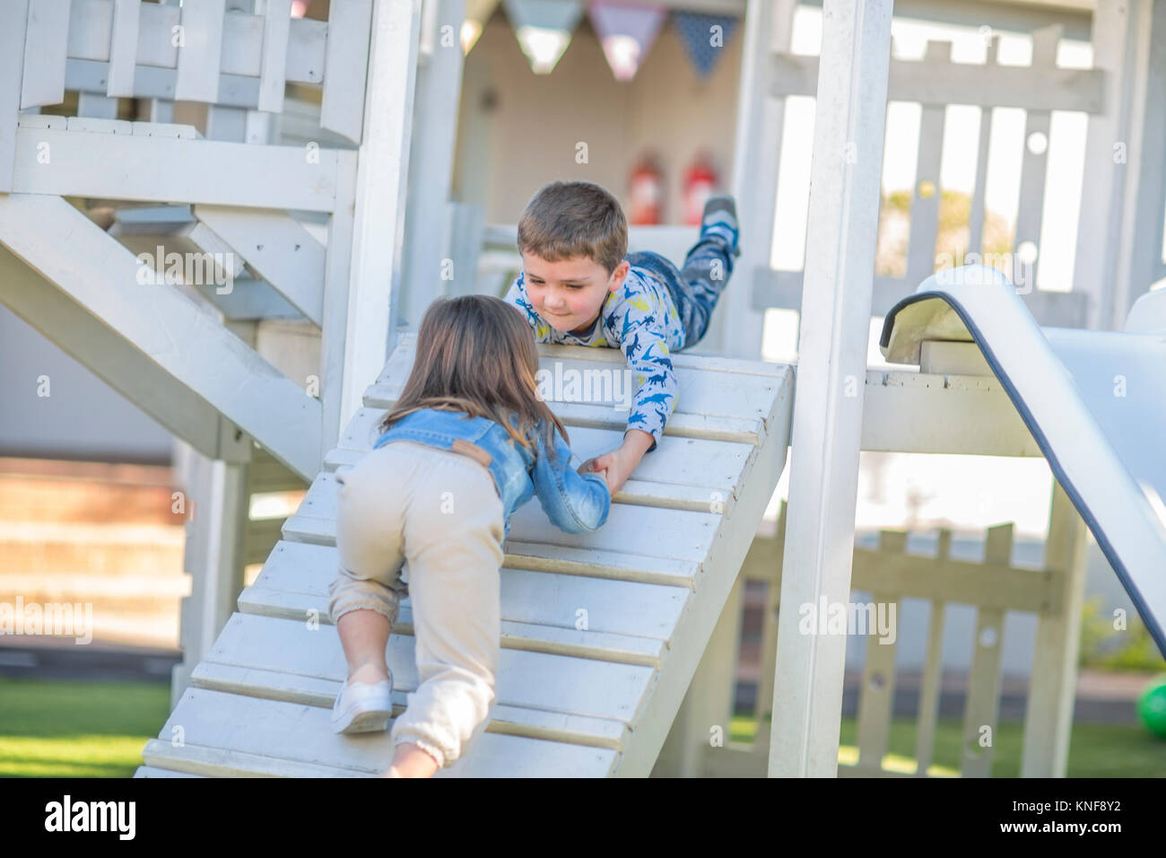 Girl and boy at preschool, helping hand to crawl up ramp on climbing frame in garden - Stock Image
