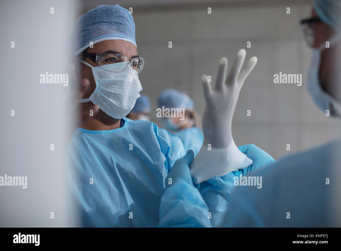Surgeons preparing for surgery, putting on latex gloves - Stock Image