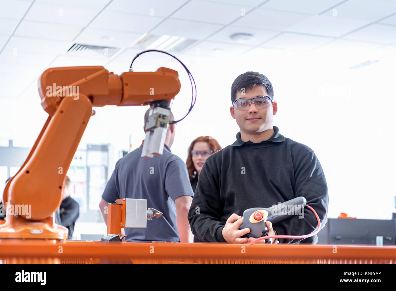 Portrait of robotics apprentice using test industrial robots in robotics facility Stock Photo