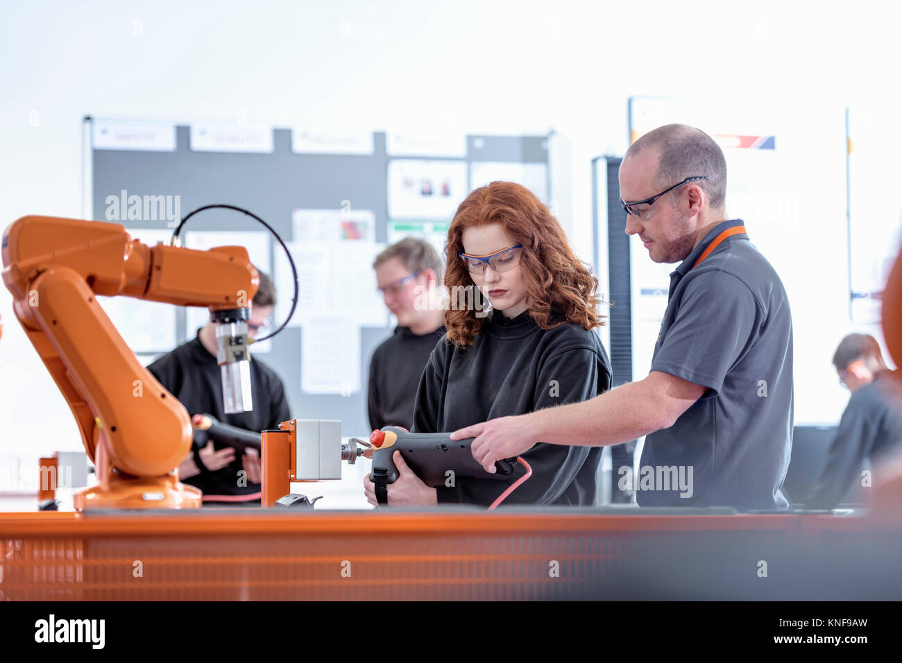 Tutor with robotics apprentices using test industrial robots in robotics facility - Stock Image