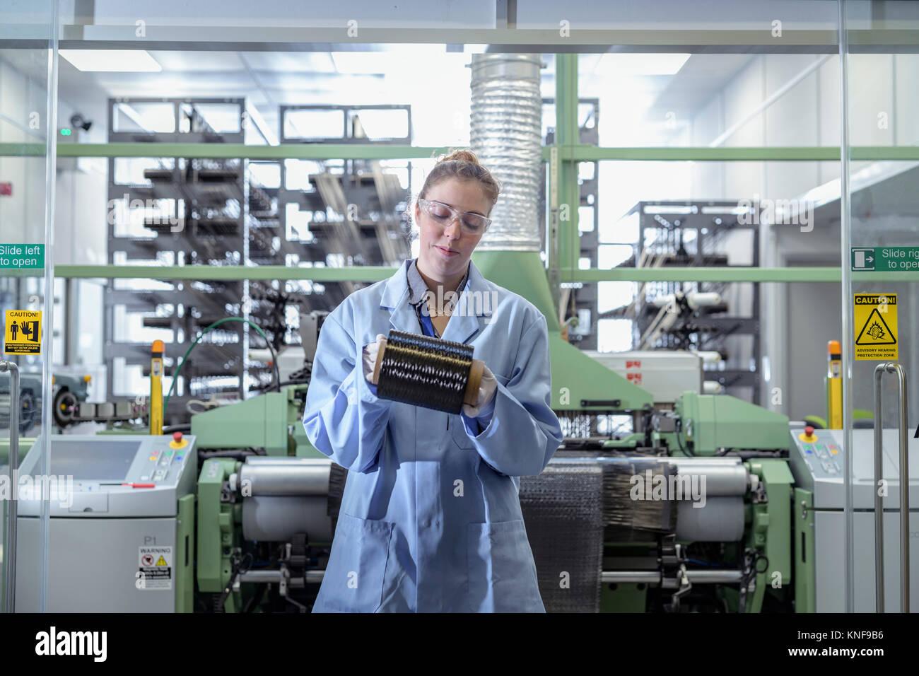 Female operator with bobbin of carbon fibre in carbon fibre production facility - Stock Image