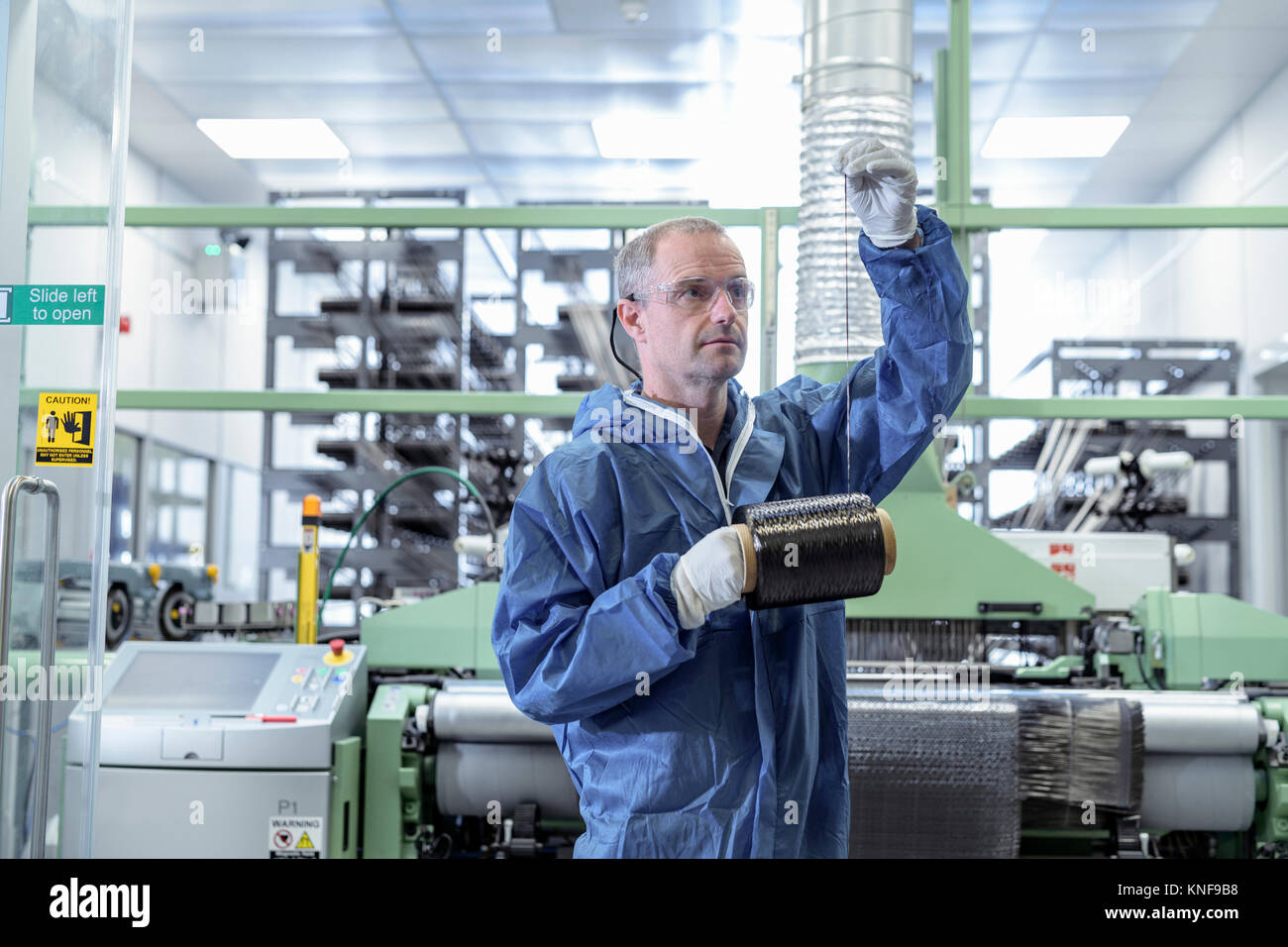 Operator with bobbin of carbon fibre in carbon fibre production facility - Stock Image