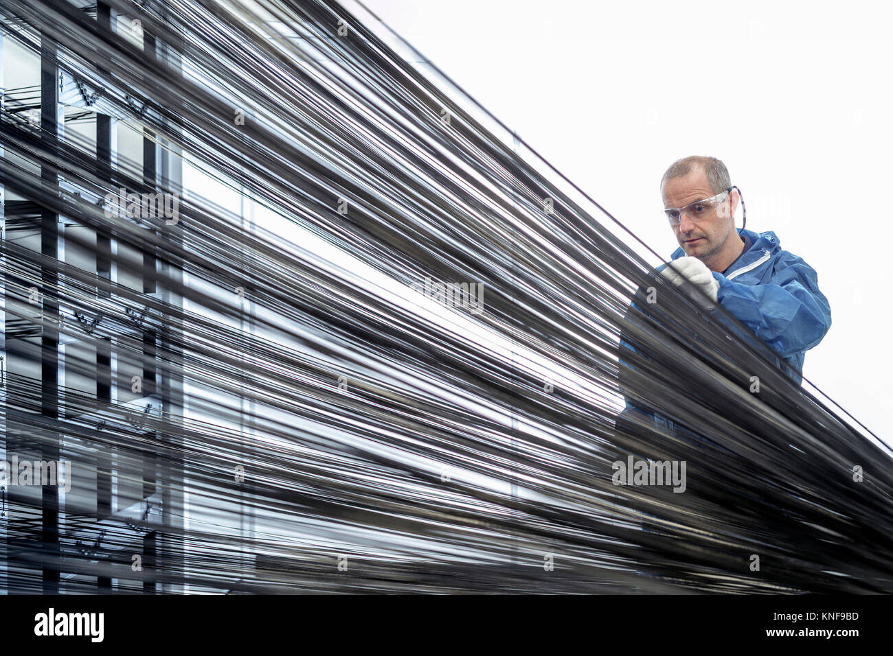 Operator with carbon fibre thread on loom in carbon fibre production facility - Stock Image