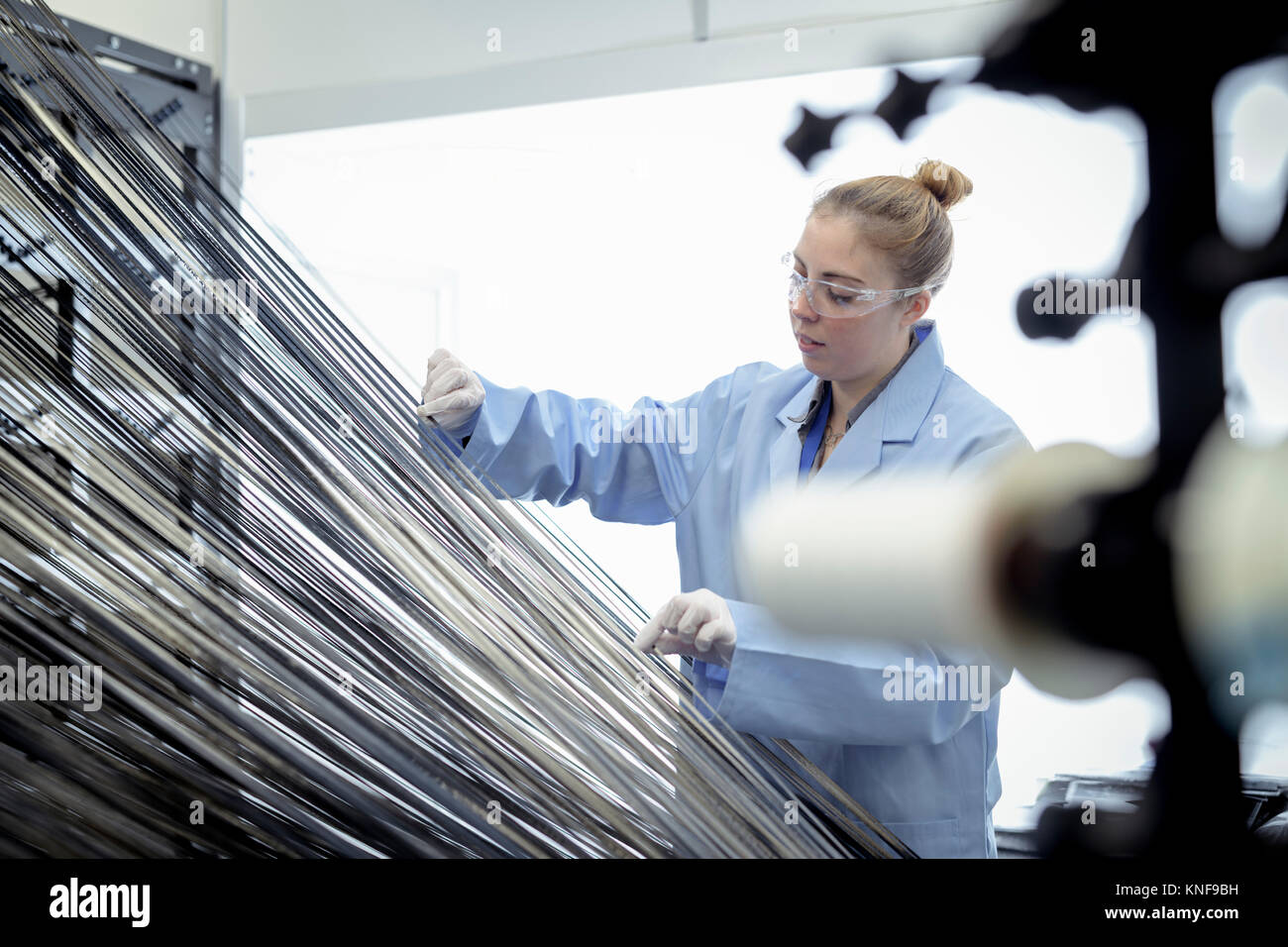 Female operator with carbon fibre thread on loom in carbon fibre production facility Stock Photo