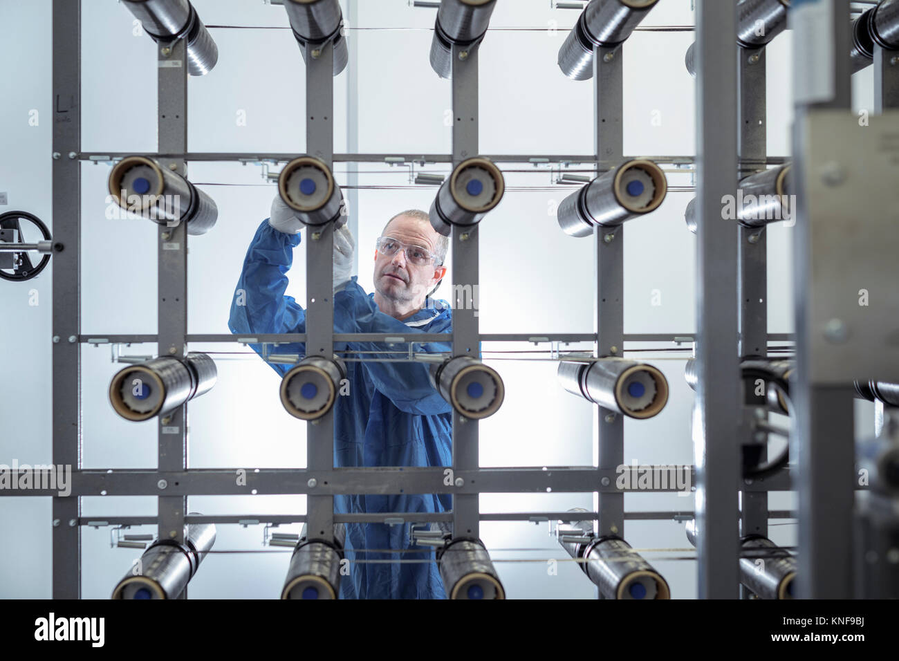 Operator with carbon fibre bobbins on loom in carbon fibre production facility - Stock Image