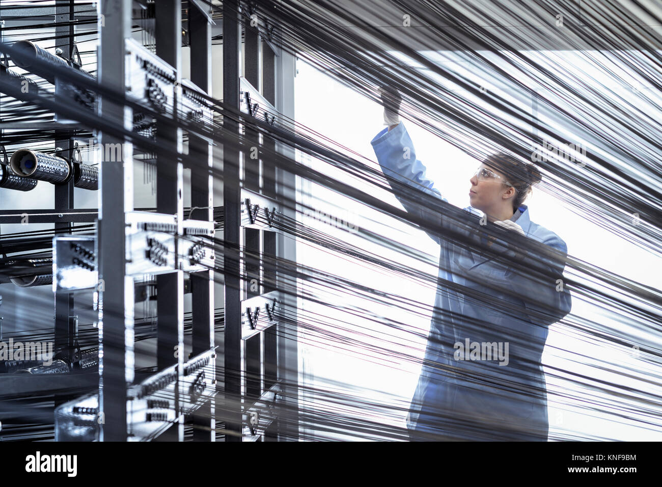Female operator with carbon fibre thread on loom in carbon fibre production facility - Stock Image