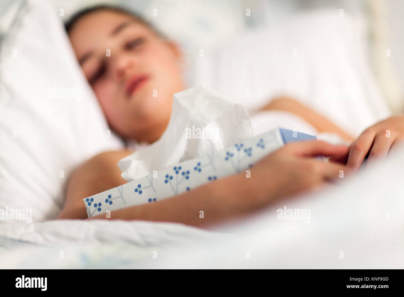 Girl in bed holding box of tissues - Stock Image