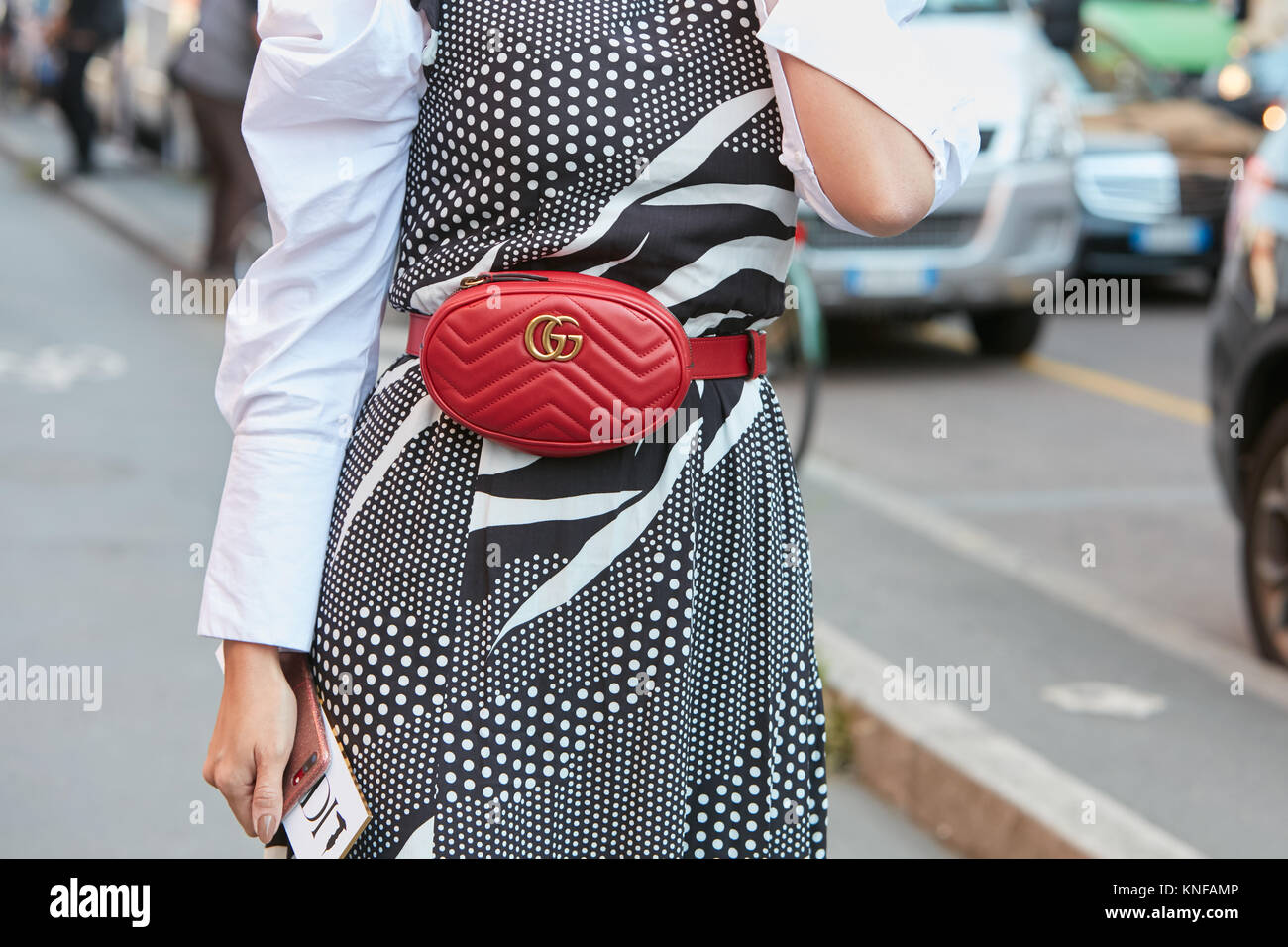 MILAN - SEPTEMBER 24: Woman with Gucci red leather pouch and black and white dress before Trussardi fashion show, - Stock Image