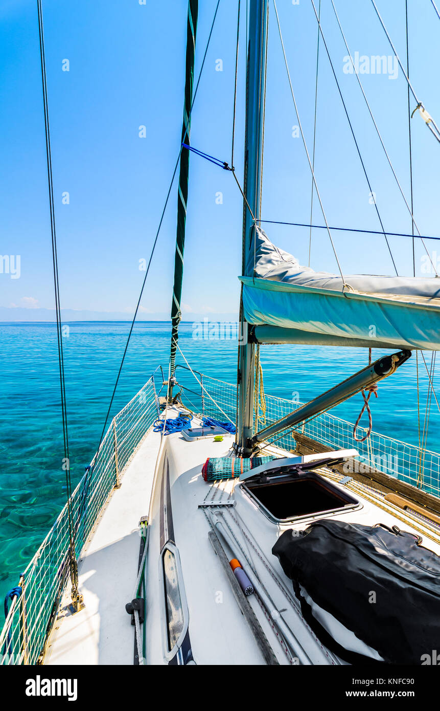 Front view of sailing boat on the sea. Bow side of yacht or sail boat gliding through calm sea in Adriatic sea on - Stock Image