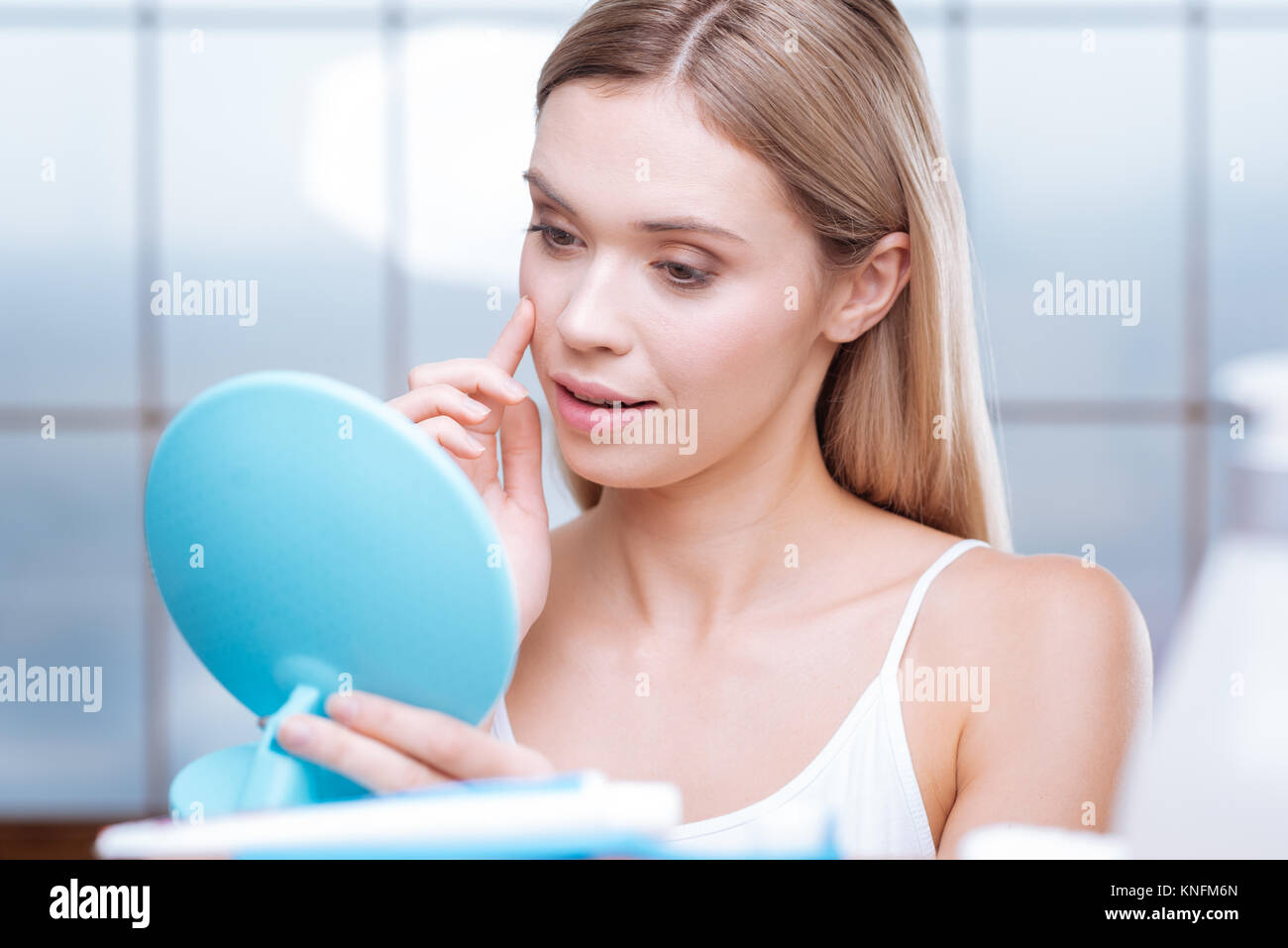 Pretty young woman touching skin on her cheek - Stock Image