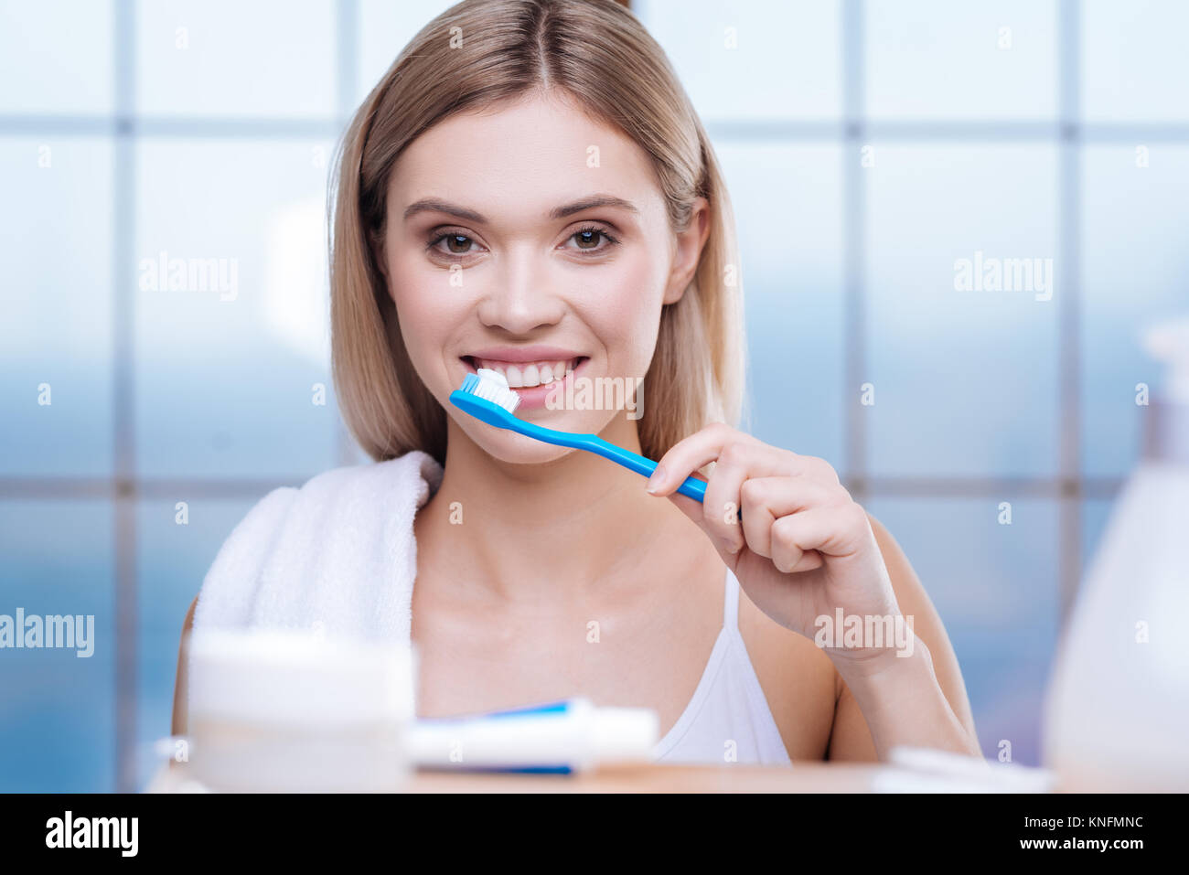 Upbeat young woman brushing her teeth - Stock Image
