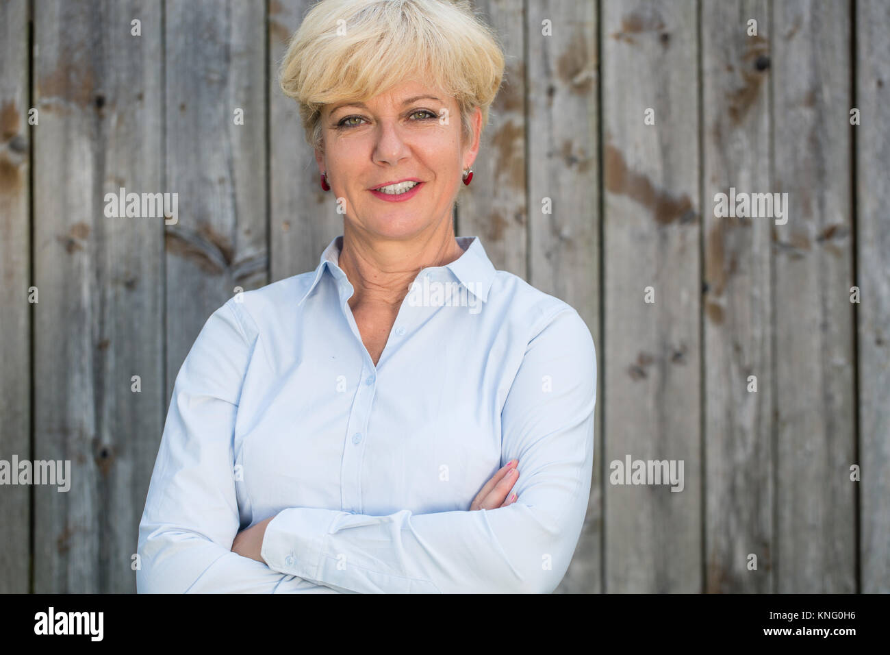 Portrait of a confident senior woman looking at camera against a Stock Photo