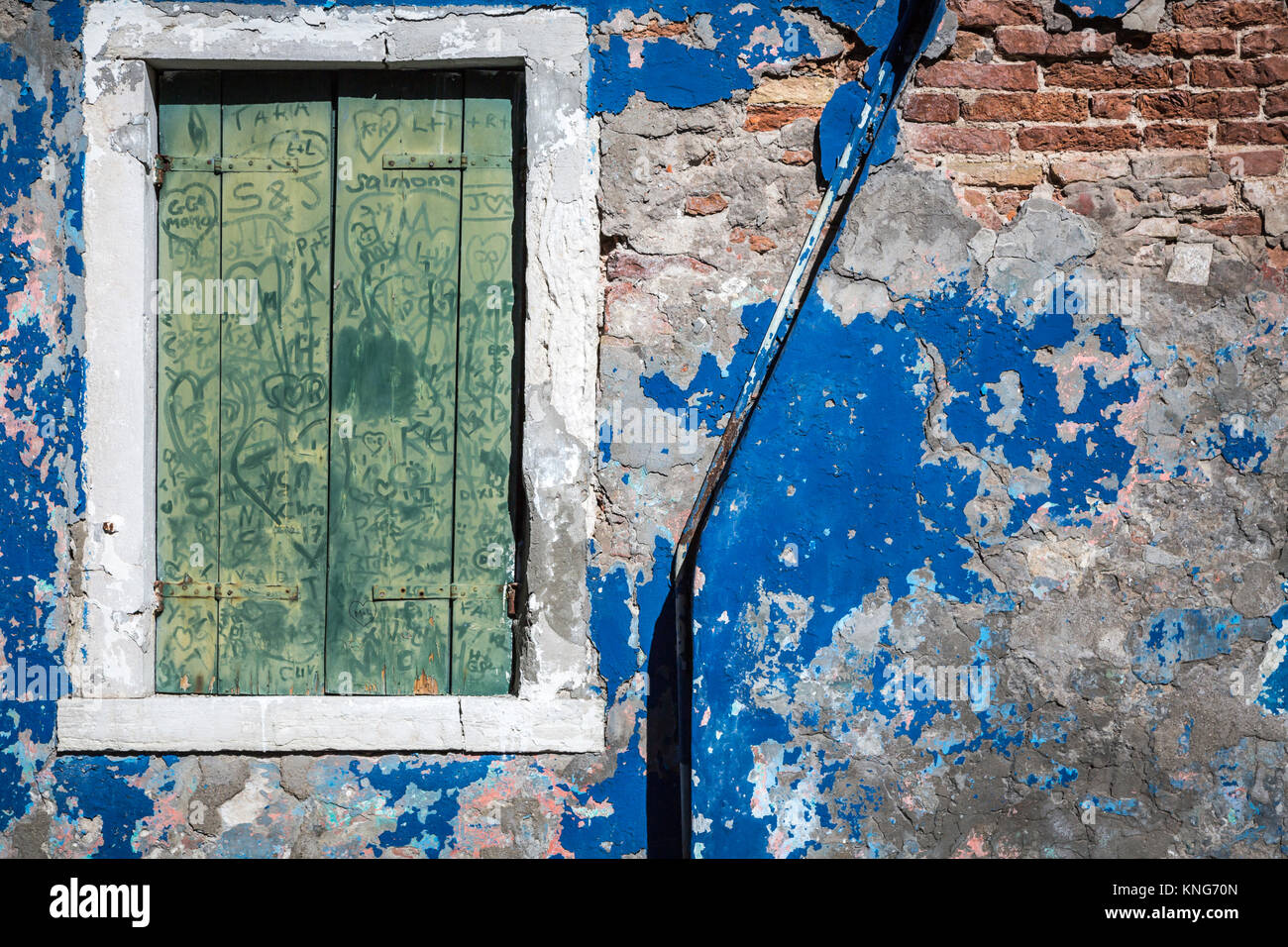 An old building with peeling paint in the Venetian village of Burano, Venice, Italy, Europe. - Stock Image