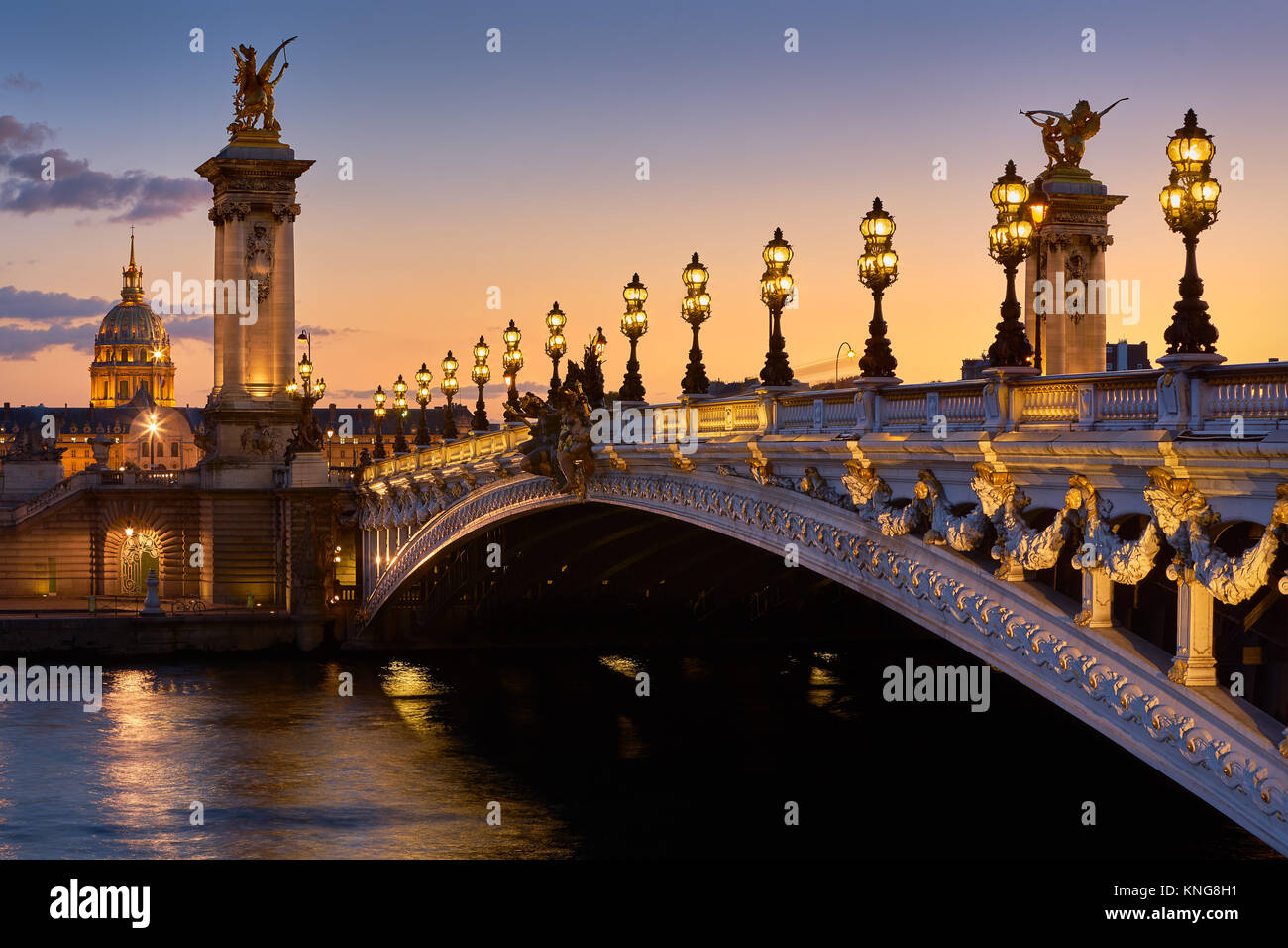 Pont Alexandre III Bridge and illuminated lamp posts at sunset with view of the Invalides. 7th Arrondissement, Paris, Stock Photo