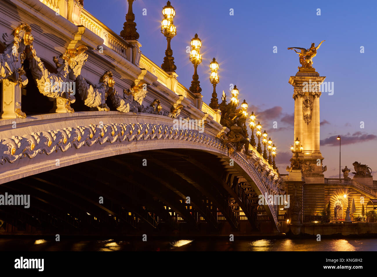 Close-up of Pont Alexandre III Bridge and illuminated lamp posts at sunset. 7th Arrondissement, Paris, France - Stock Image