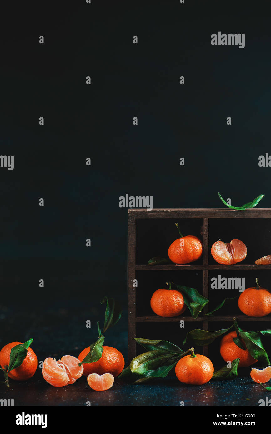 Tangerines in a wooden shadow box on a dark background. Dark food photography with vibrant orange fruit and copy - Stock Image