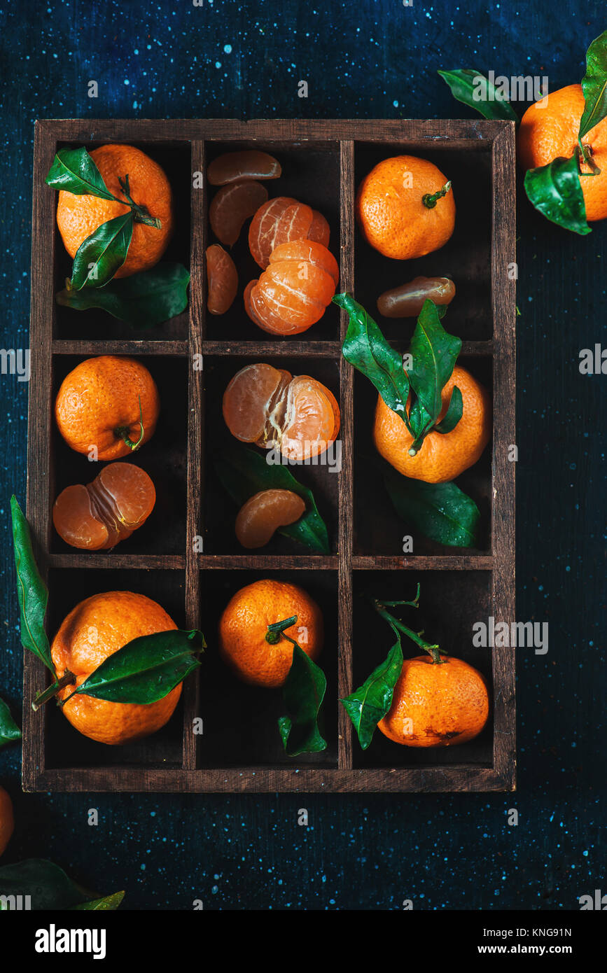 Tangerines in a wooden case on a dark background. An assortment of clementines with green leaves. Dark food photography - Stock Image