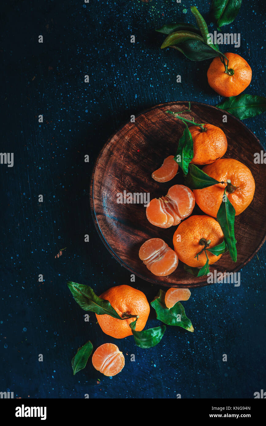 Citrus fruits on a wooden plate with green leaves. Vibrant tangerines on a dark background. Rustic food photography. Stock Photo