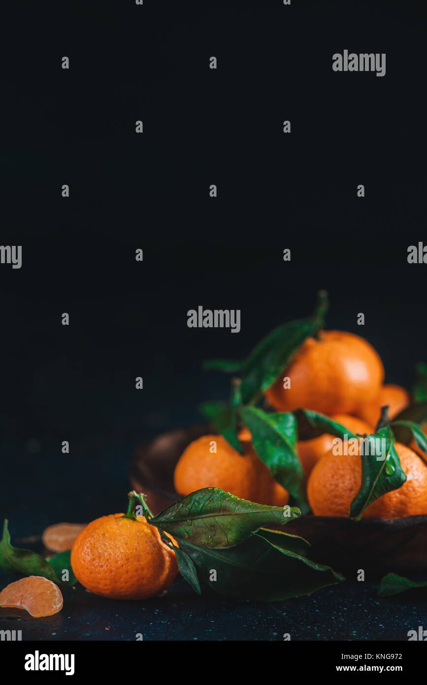 Citrus fruits on a wooden plate with green leaves. Vibrant tangerines on a dark background. Rustic food photography. - Stock Image