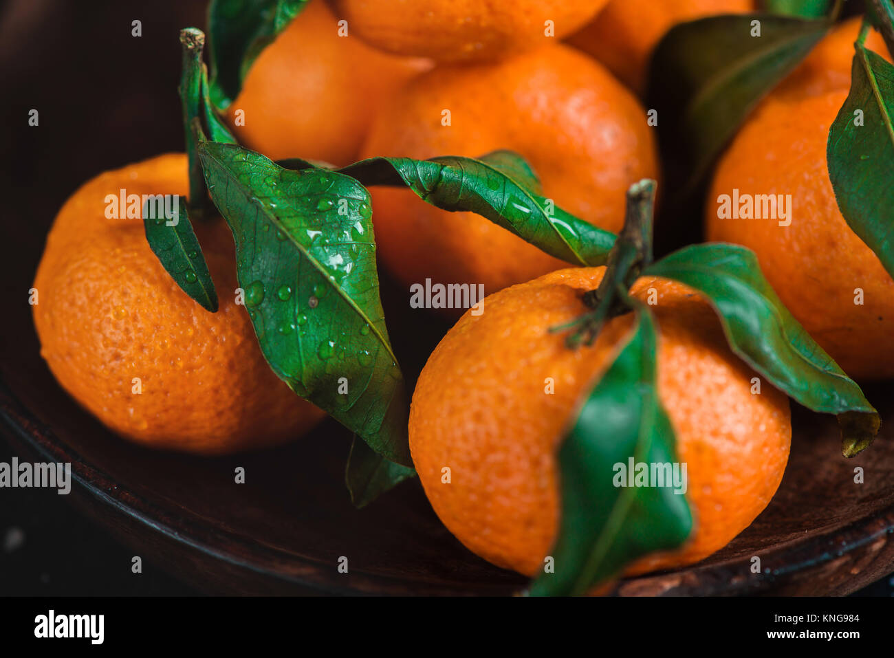 Close-up of tangerines in a wooden plate on a dark background. Water drops on a surface. Rustic food photography - Stock Image