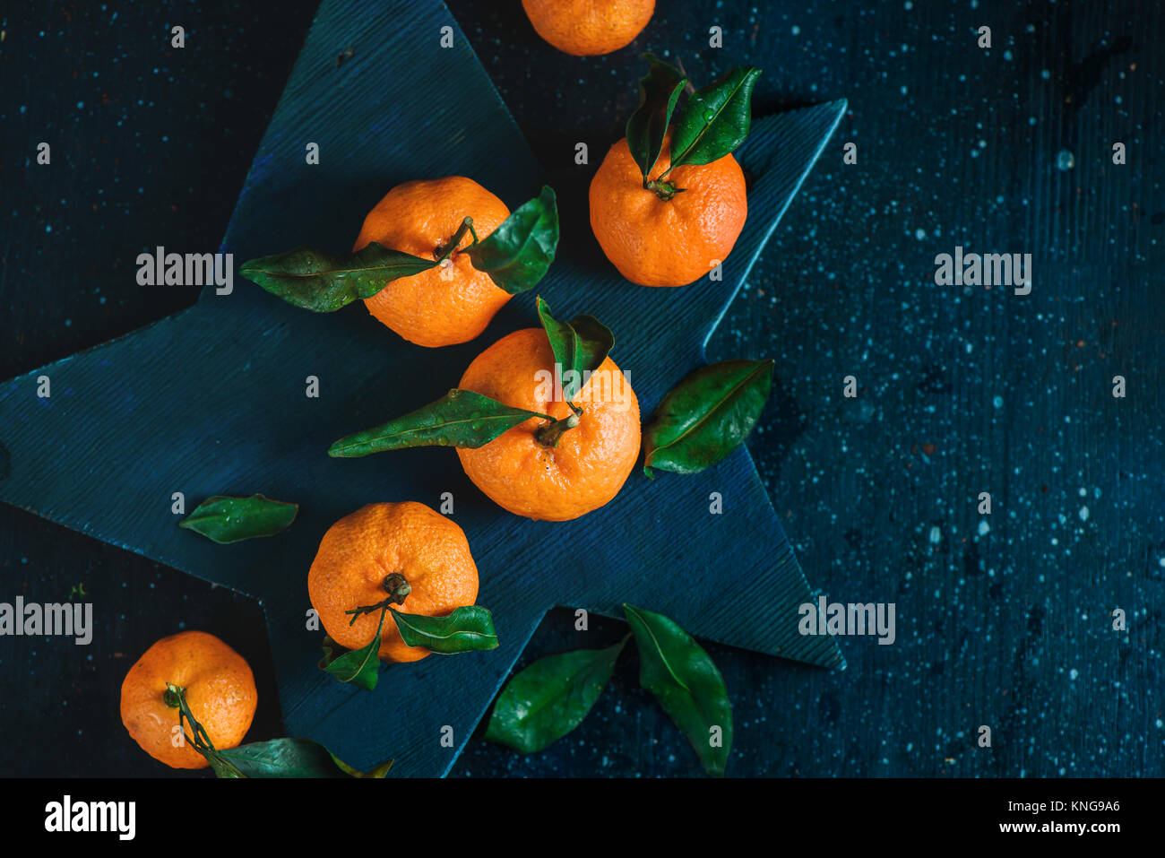Orange tangerines with green leaves on a star-shaped cutting board. Vibrant fruits on a dark background. Rustic - Stock Image