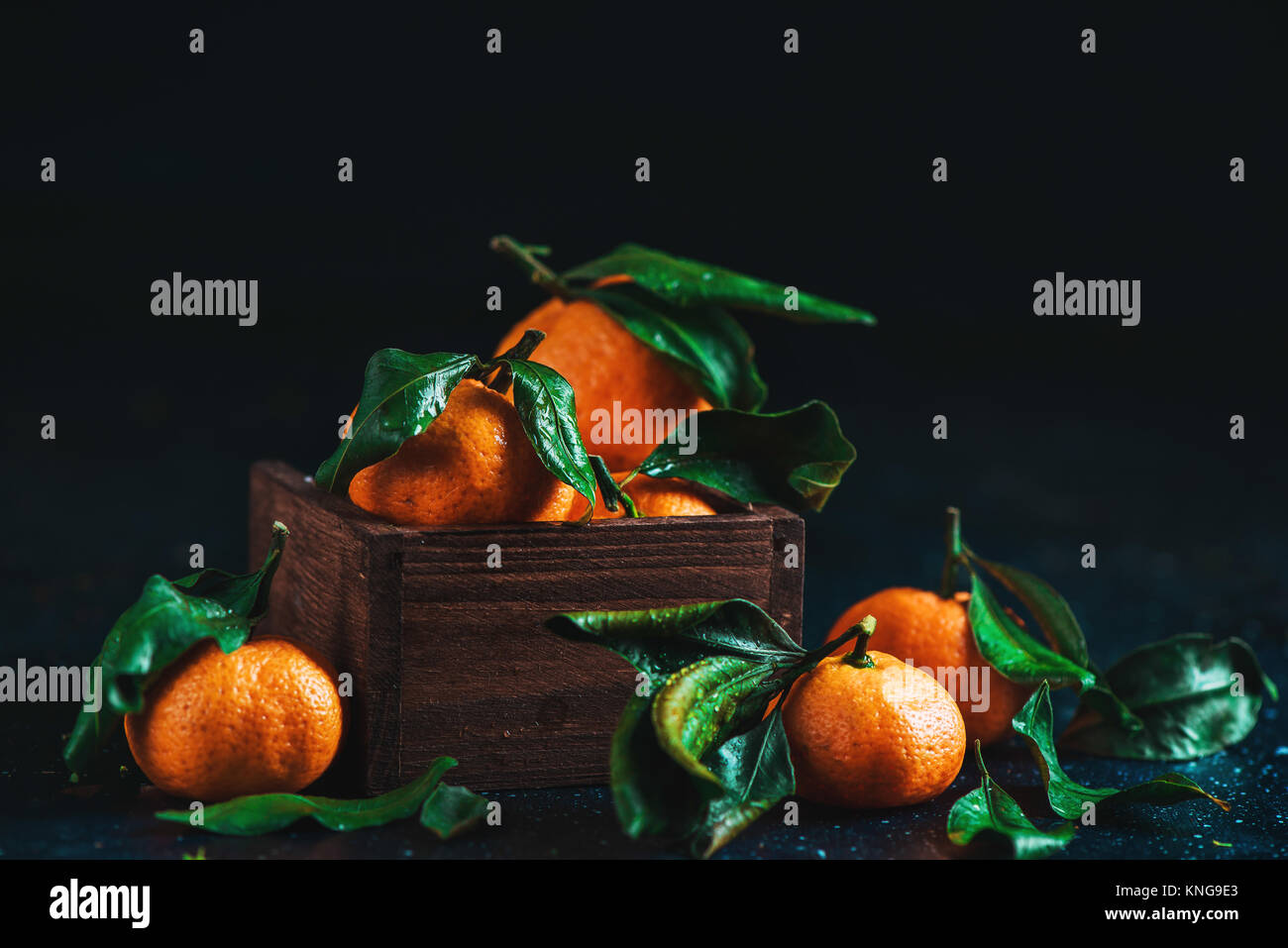 Tangerines in a wooden box on a dark wooden background. Vibrant ripe fruit concept. Dark food photography. - Stock Image