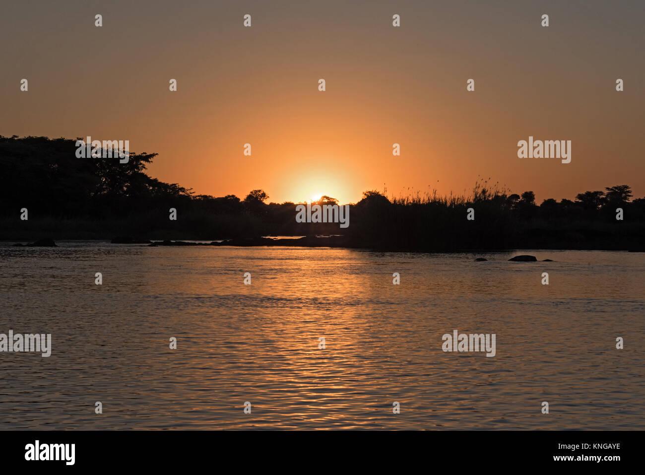 sunset on the okavango river in namibia - Stock Image