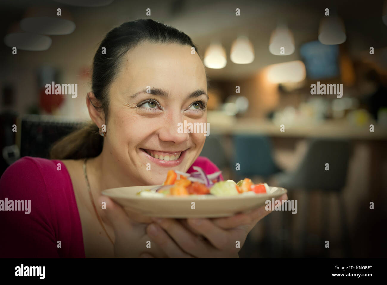 Portrait of a young attractive woman eating salad at cafe table. Horizontal shot.Beautiful young female enjoying Stock Photo