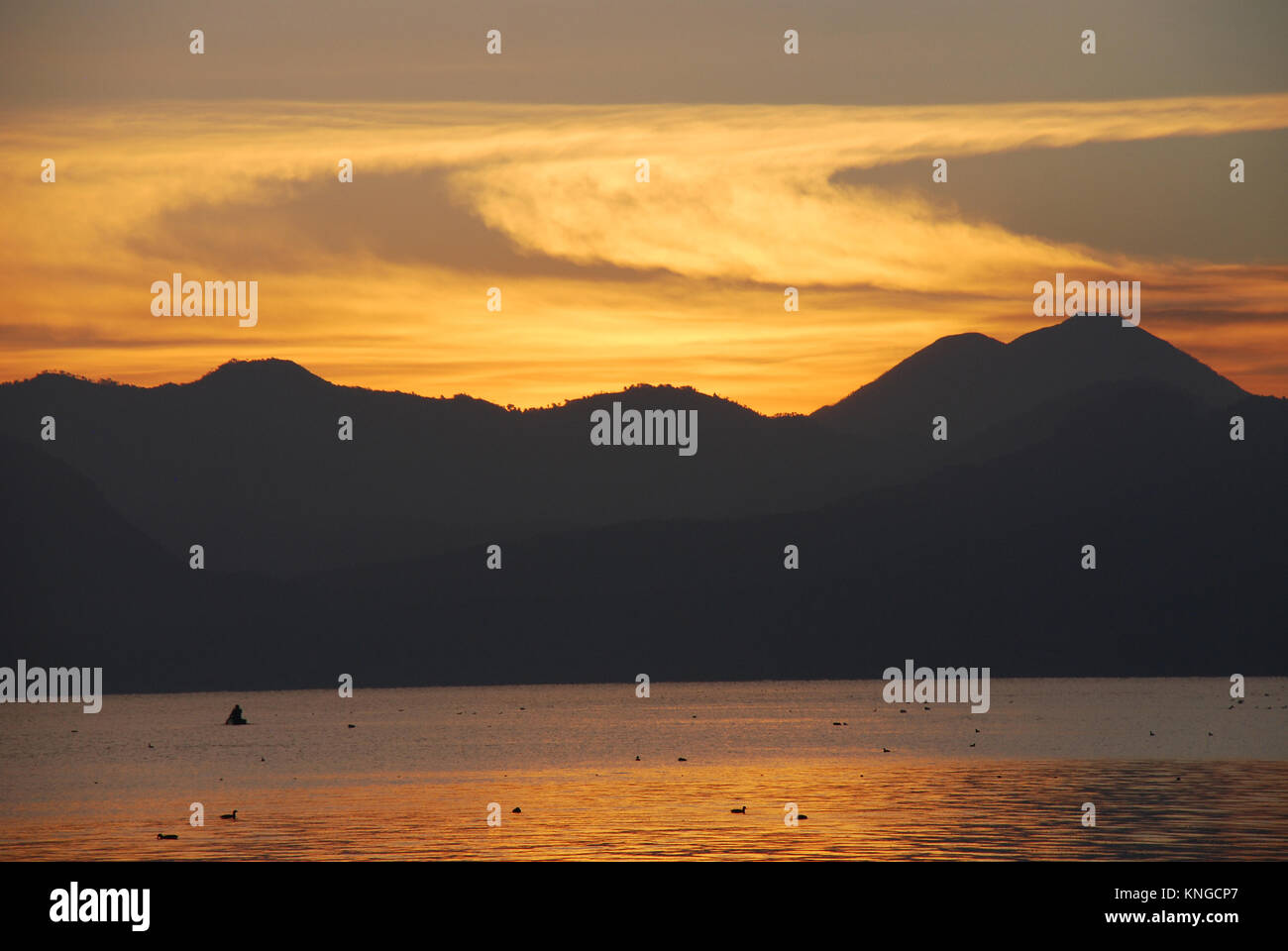 Sunrise at Lake Atitlan in Guatemala which is surrounded by high cliffs and overlooked by three volcanoes - Stock Image