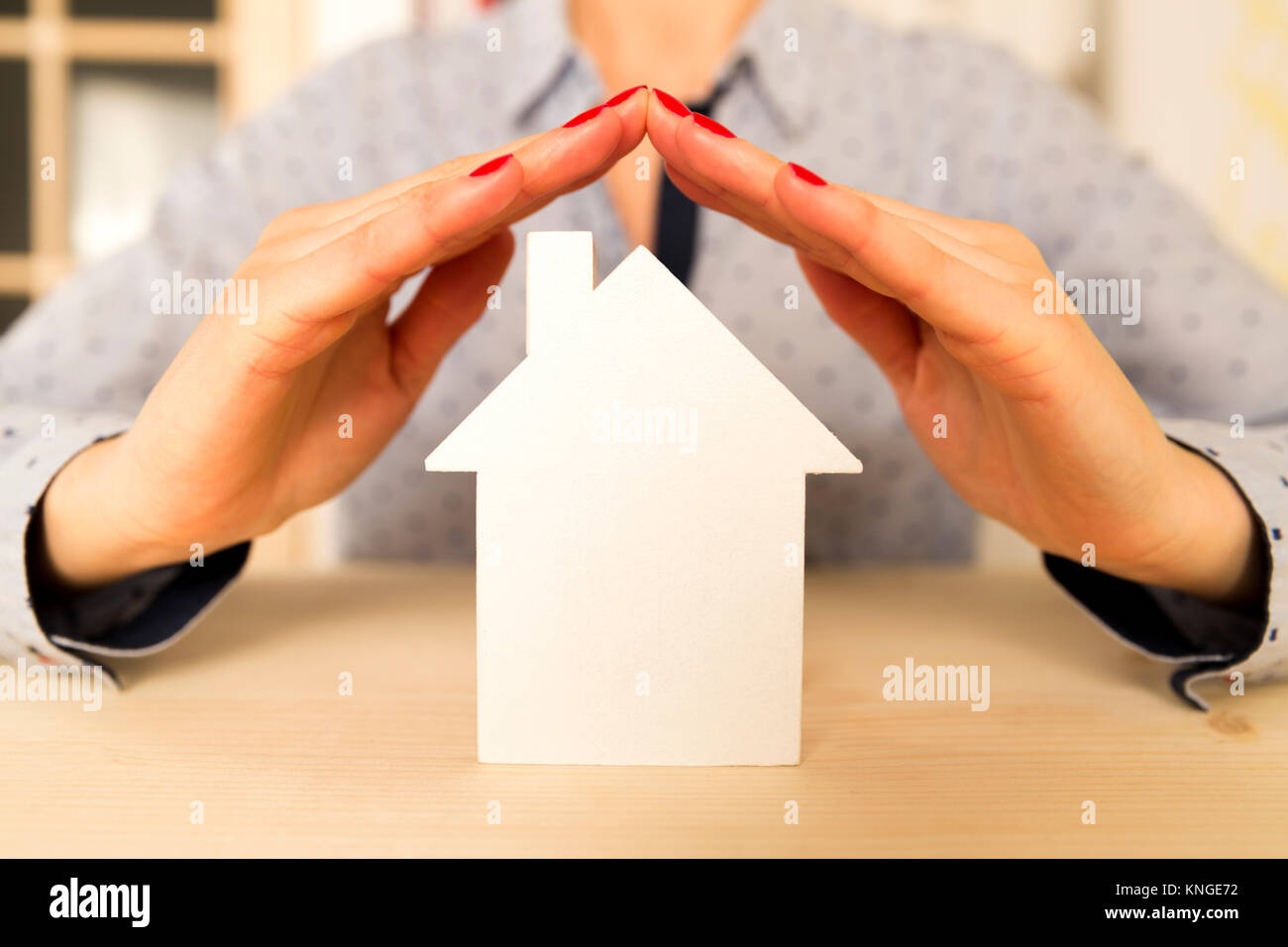 Woman holding her hands above white small model house as a sign of home protection and insurance - Stock Image