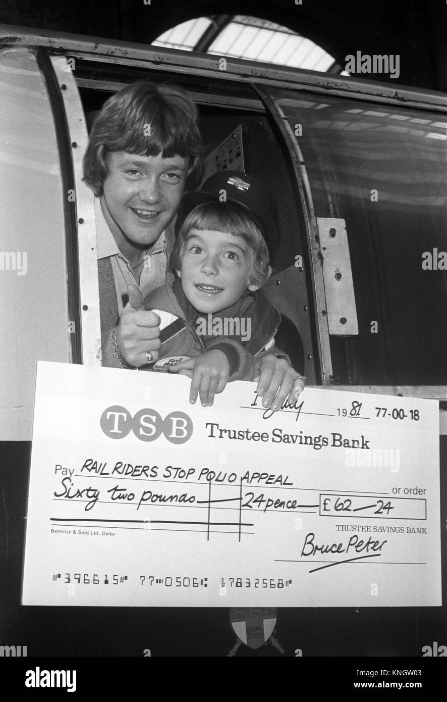 Bruce Peter (r), the seven-year-old from Airdrie, Scotland, hands children's TV star Keith Chegwin a cheque - Stock Image