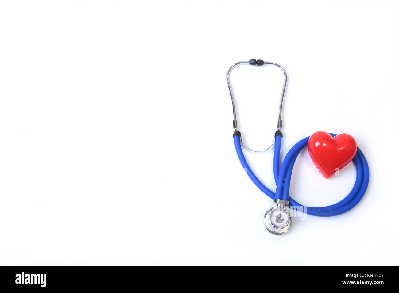 Heart with a medical stethoscope, isolated on wooden background - Stock Image