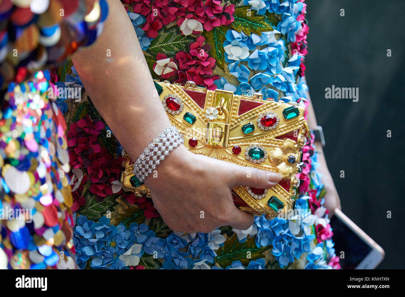 MILAN - SEPTEMBER 24: Woman with golden Dolce and Gabbana bag with jewels decoration and floral dress before Dolce - Stock Image