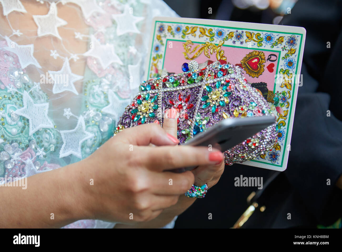 MILAN - SEPTEMBER 24: Woman with bag decorated with colorful gems and beads looking at phone before Dolce and Gabbana - Stock Image