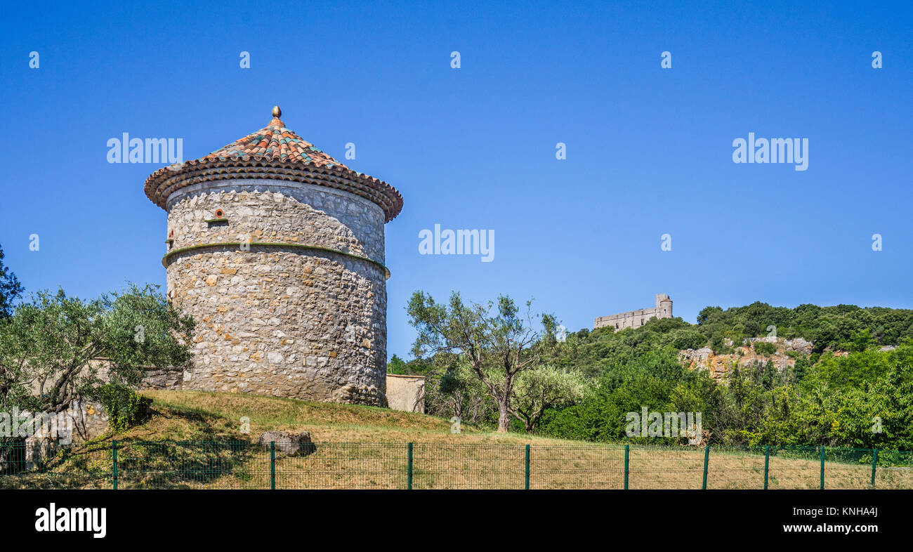 France, Region Occitanie, Gard department, Occitan Round Tower at La Madeleine against the backdrop of  Chateau - Stock Image