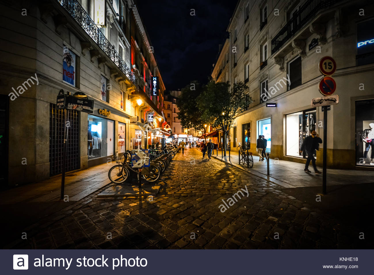 A row of bicycles for rent on a colorful street in the Latin Quarter of Paris France late at night - Stock Image