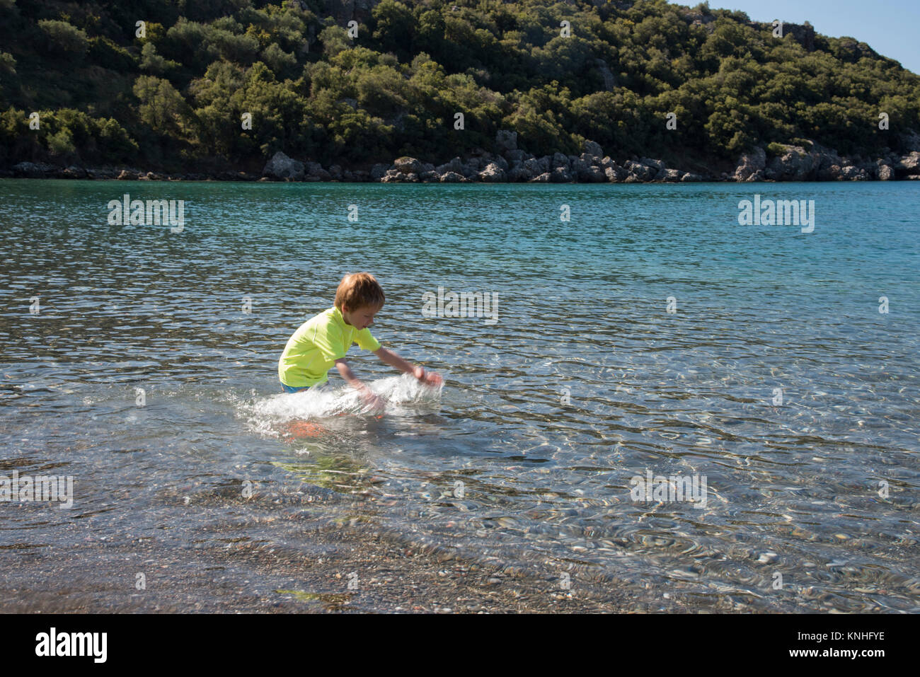 5 year old bot playing on the beech on holiday wearing sun protective beach swim wear - Stock Image