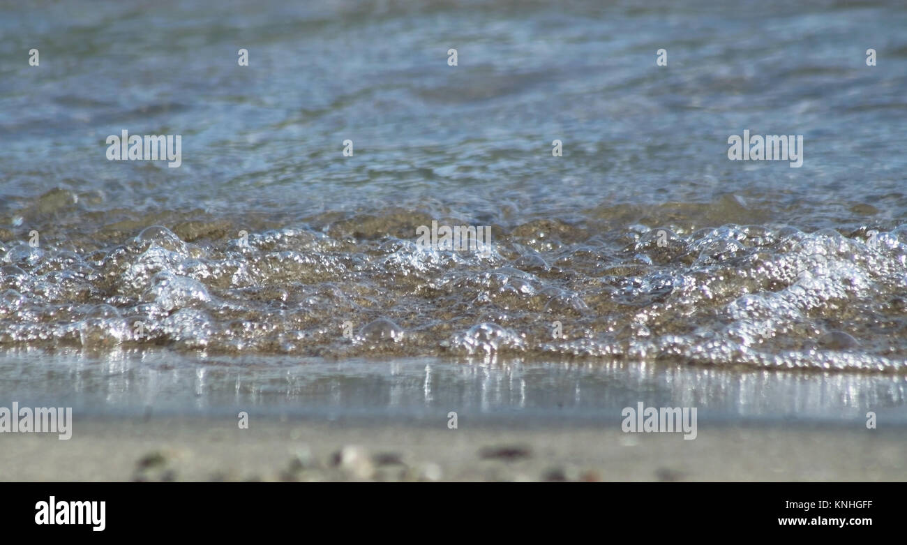 Water rolling up to sandy beach edge at eye level Stock Photo