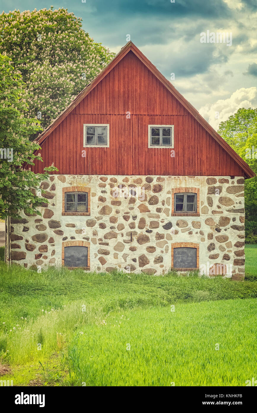 An old stone barn with wooden roof set in the rural countryside of Swedens Skane region. - Stock Image