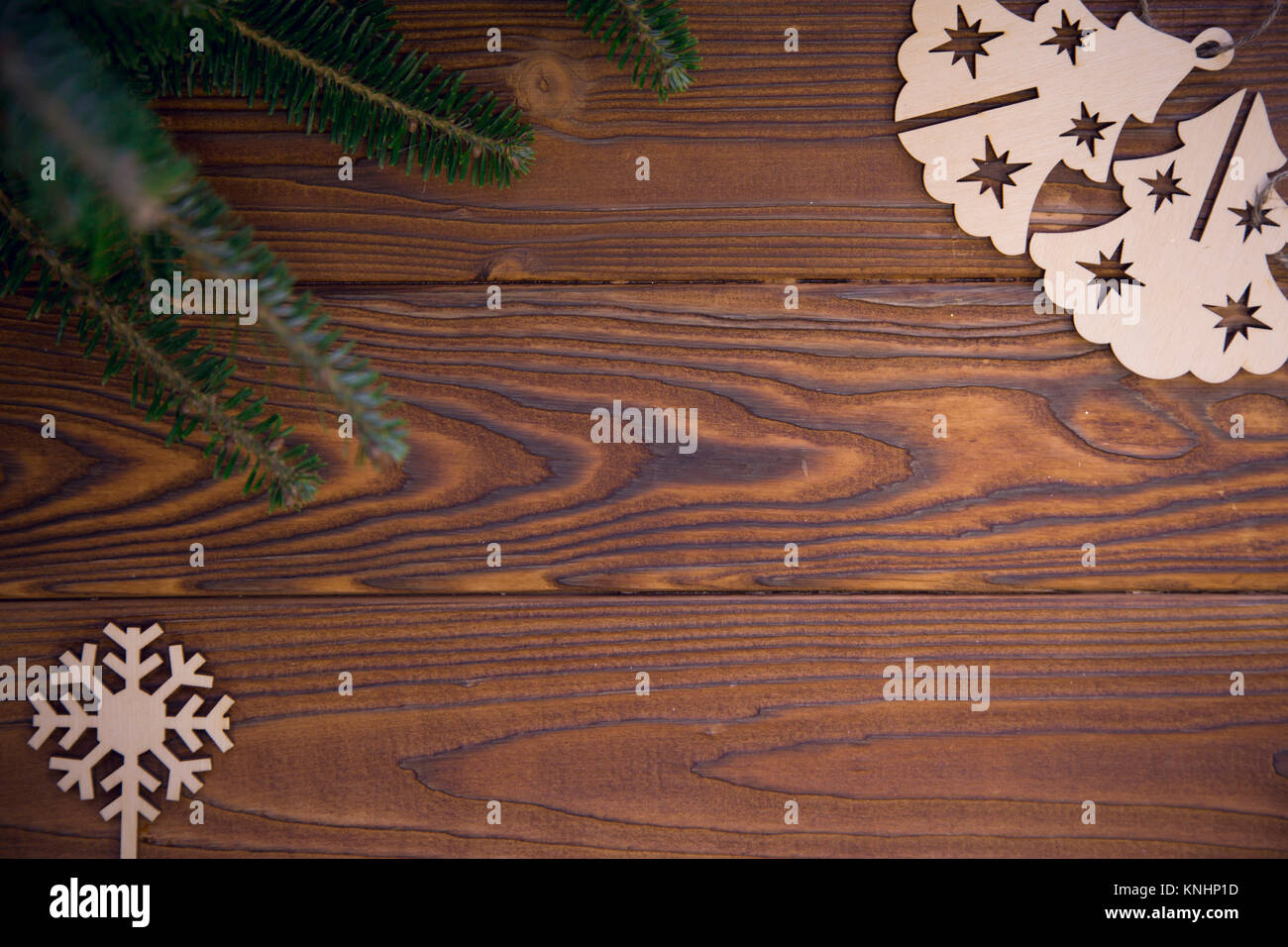 rustic wooden christmas or new year background with natural green fir tree branches and wooden flat christmas tree toys