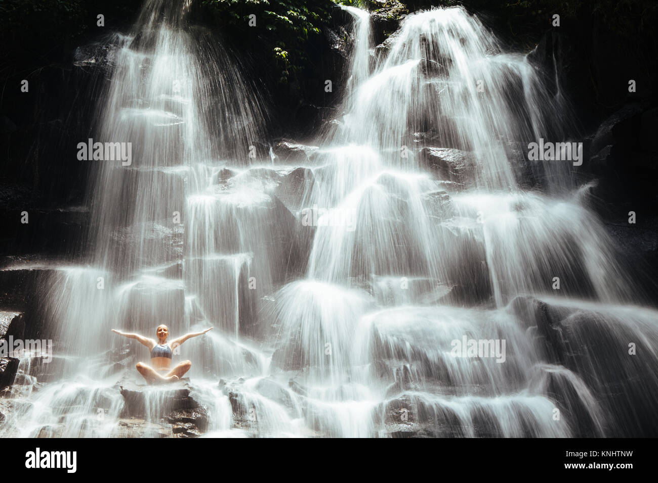 Travel in Bali jungle. Beautiful young woman sitting in yoga pose on rock under falling spring water, enjoy tropic - Stock Image