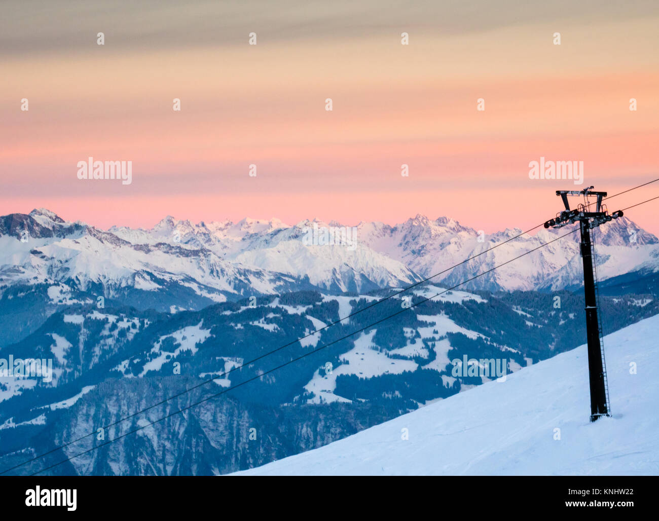 winter landscape in the Swiss Alps with a ski resort and chairlift in the foreground under a beautiful evening sky - Stock Image