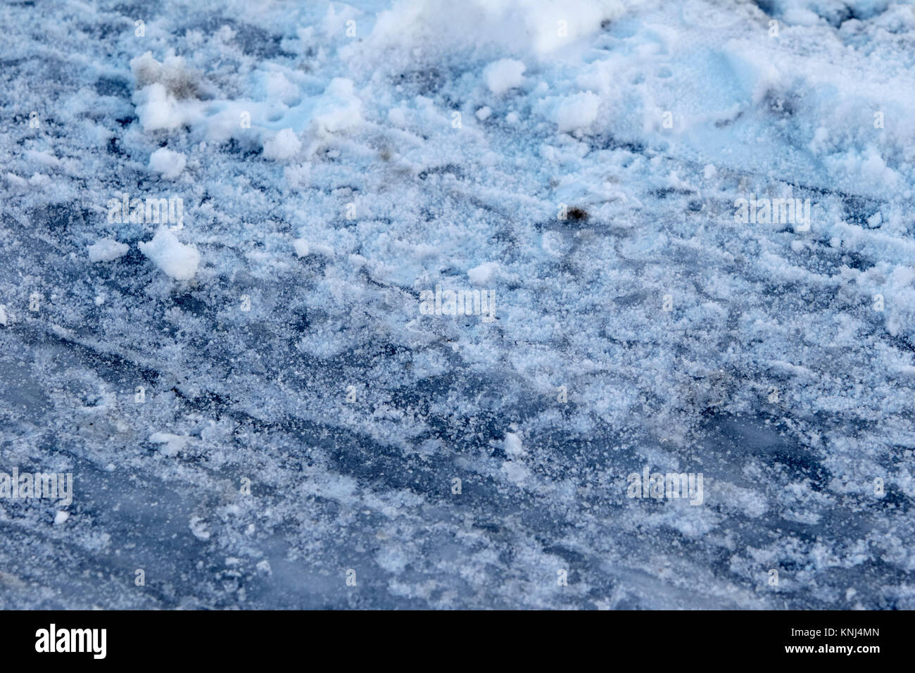 tyre tracks in compacted snow showing black ice underneath newtownabbey northern ireland uk - Stock Image