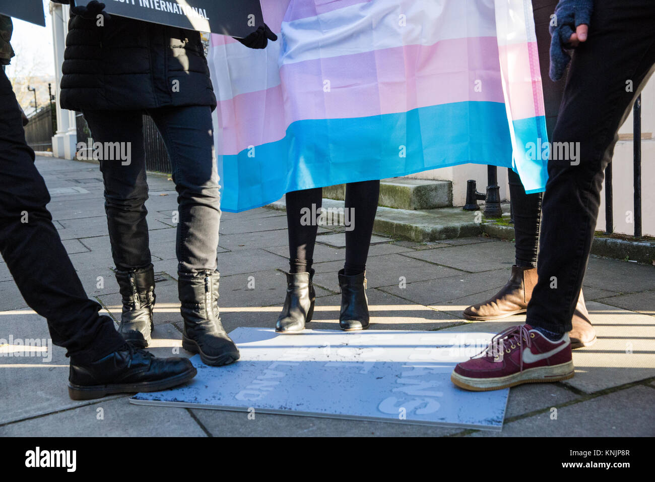 London, UK. 12th December, 2017. Amnesty International activists with a Transgender Pride flag stand on a placard Stock Photo